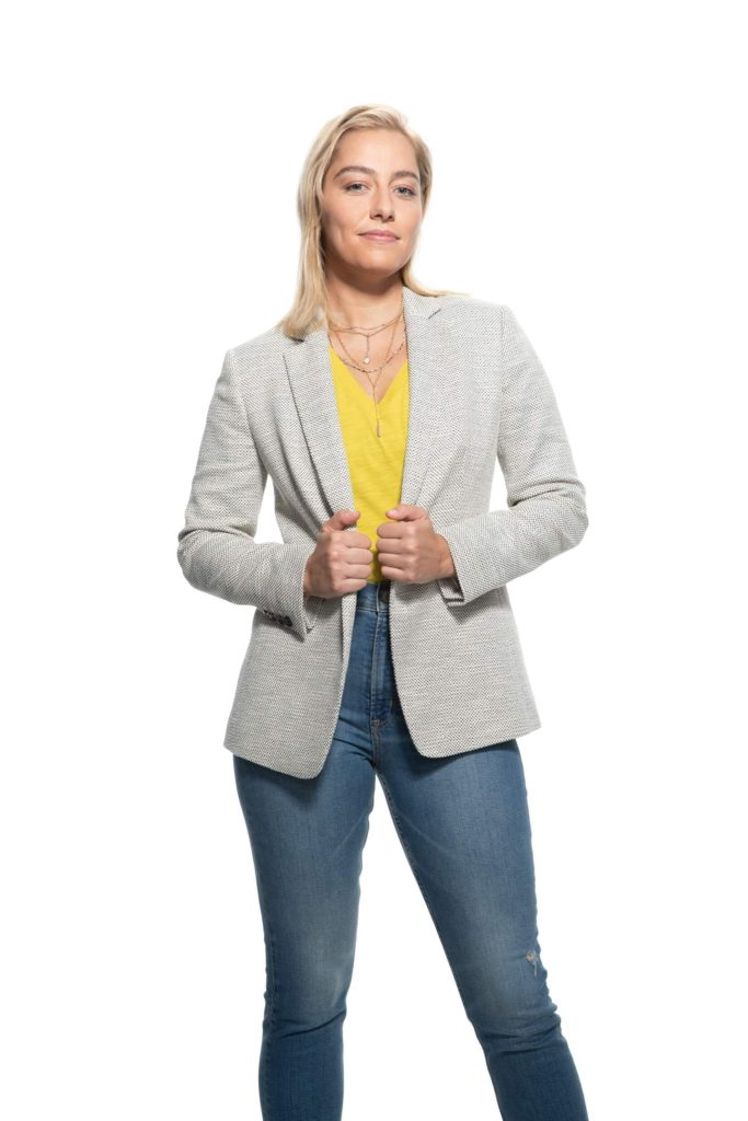 Woman with individual insurance standing confidently with jeans and a jacket
