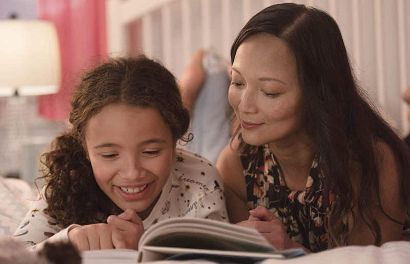 Mother reading story to daughter
